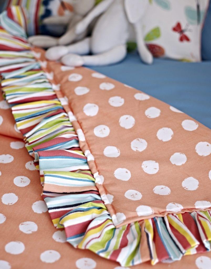 Orange children's bedspread with cream dots.