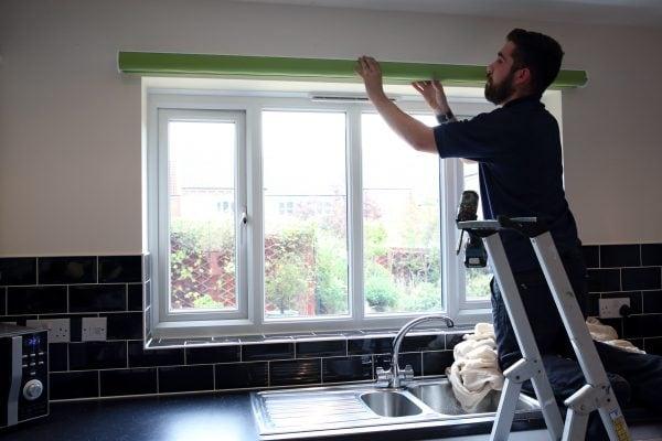 Fitter on ladder fitting a kitchen roller blind