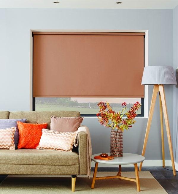 copper coloured roller blind behind sofa in living room