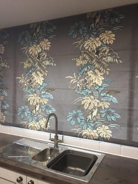 Roman blinds above a kitchen sink in pastel monkey pattern against a dark grey background