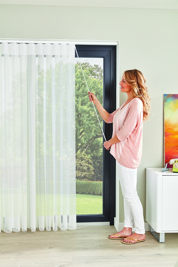Lady opening Allusion blinds using wand