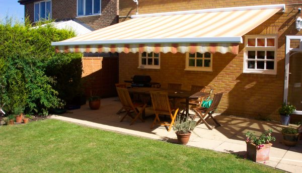 Bright stripy awnings providing shade for the garden terrace - Awnings Norfolk - Norwich Sunblinds