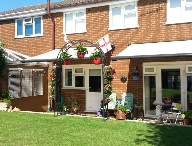 White awnings provide shade for the windows and patio doors