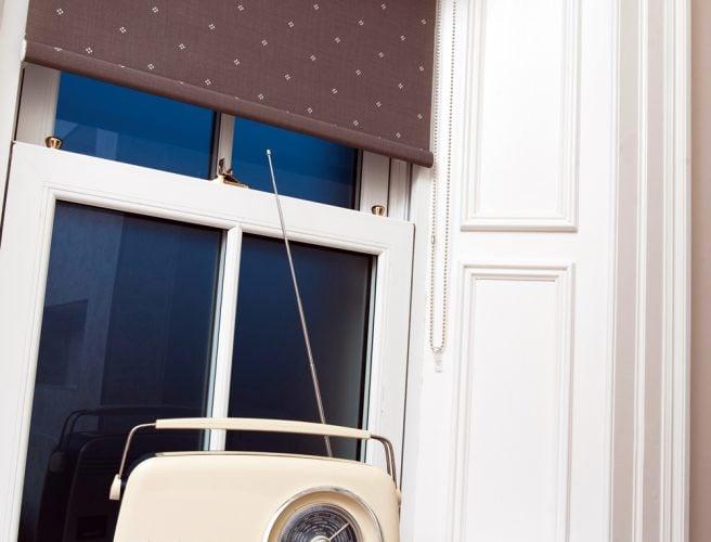 Roller blind with dark backround and fine Broderie pattern roller blind