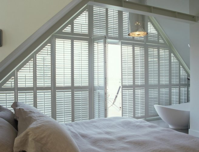 Large floor to ceiling triangular shaped window in bedroom with white shutters