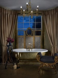 Opulent bathroom with stand alone bath and luxury curtains.