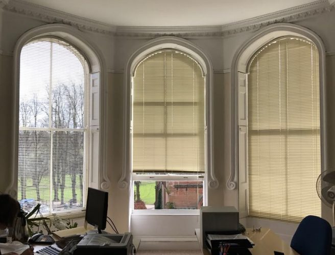Blinds fitting tall curved living room windows.