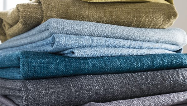 Stack of fabrics showing range of colours from greys to blue - Blinds Norfolk - Norwich Sunblindss to taupe