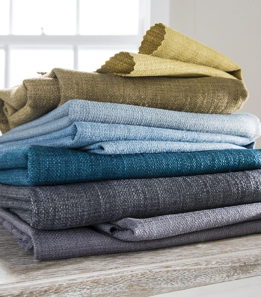 Stack of fabrics showing range of colours from greys to blues to taupe