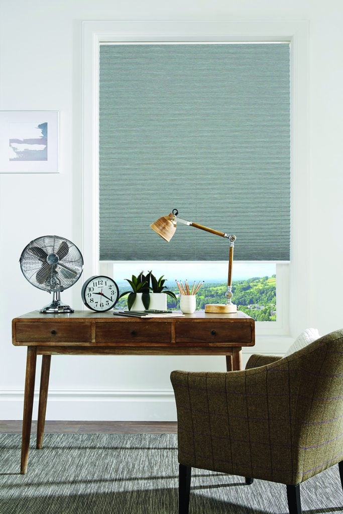 grey pleated blind behind desk and chair in home office space.