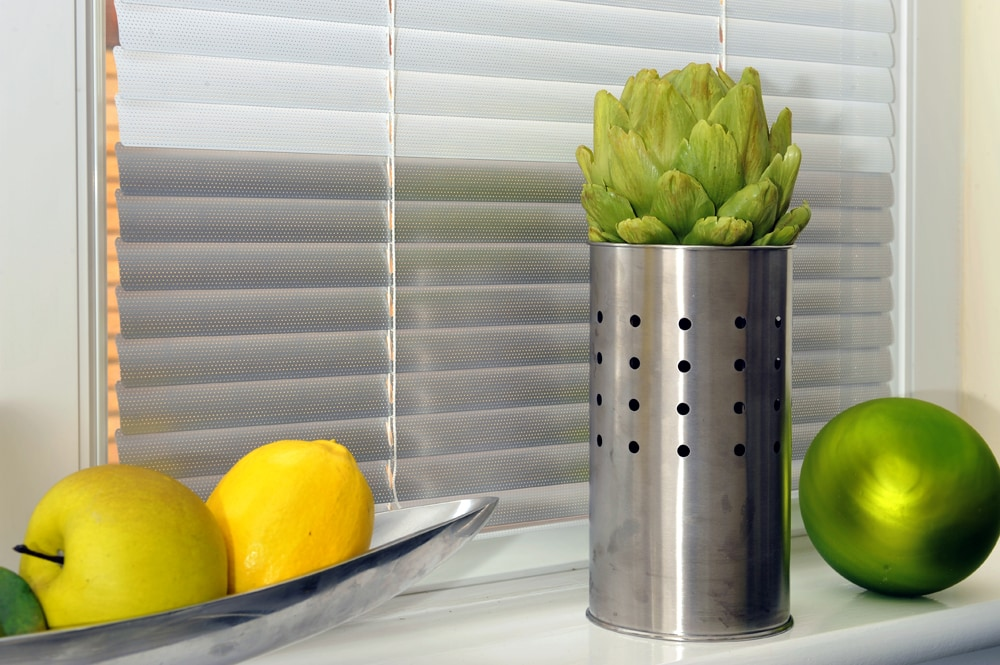 Silver grey kitchen venetian blinds with lemons and limes on window ledge.