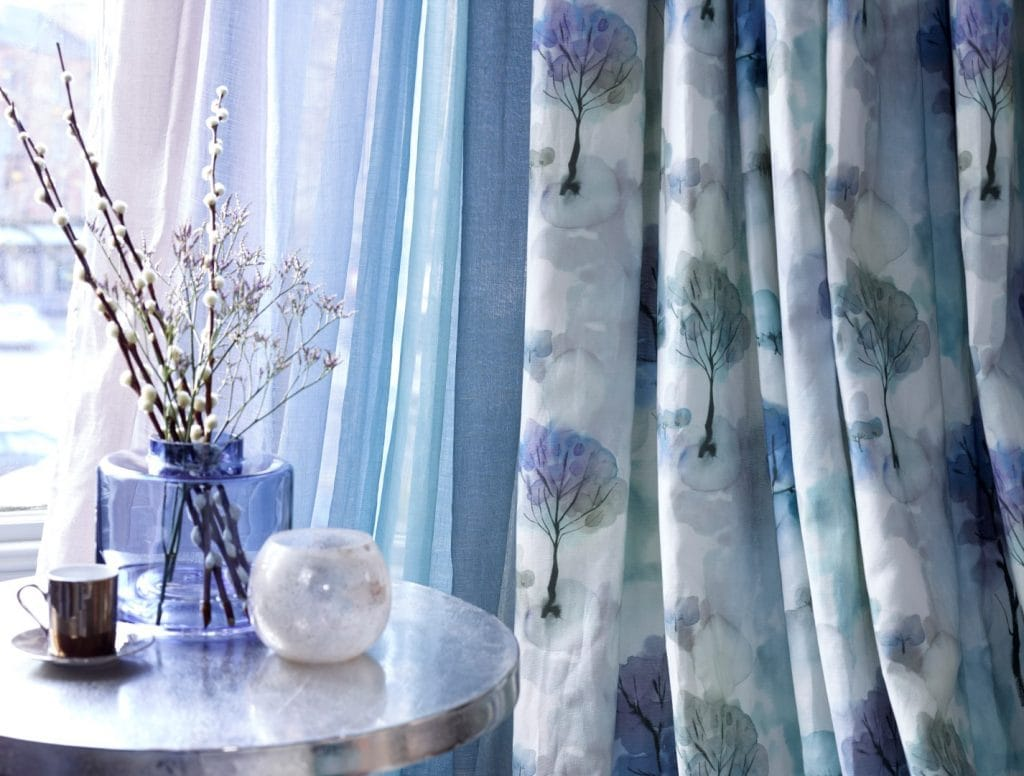 Curtains with delicate tree designs in hues of blue and green on ivory background