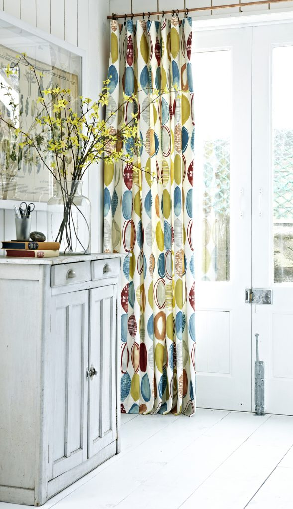 Full length curtains with brightly coloured abstract design fabric
