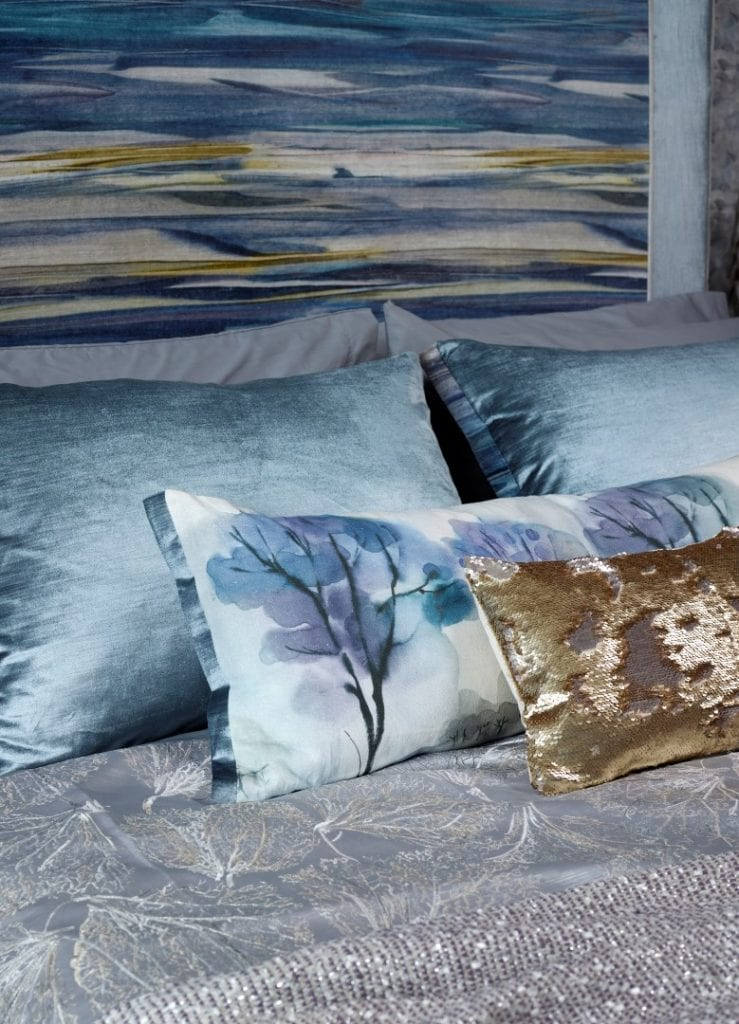 bed cover, pillows, and cushions in soft lilacs, blues and cream
