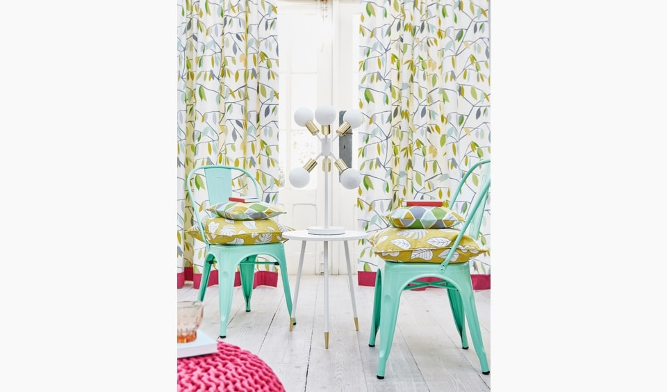 Curtains made with fabric design of light green leaves on a cream background.