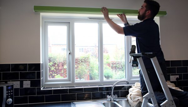Fitter on ladder fitting a kitchen roller blind