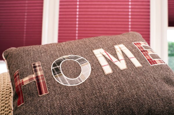 """Close up of cushion with the word """"home""""