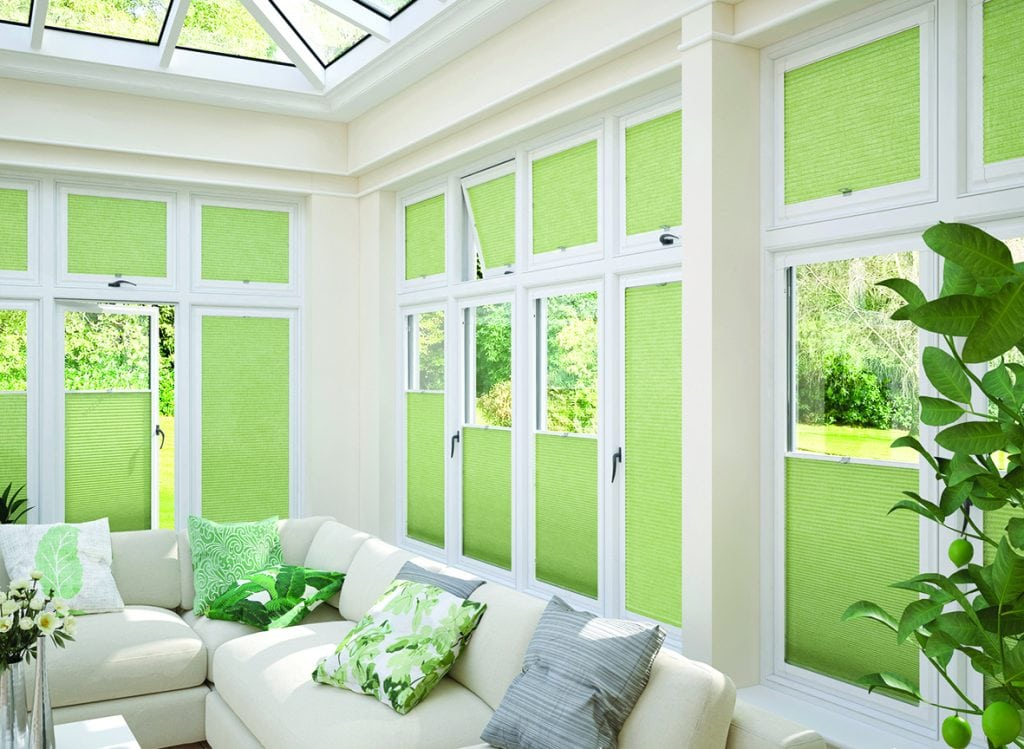 green pleated perfect fit blinds in conservatory windows.