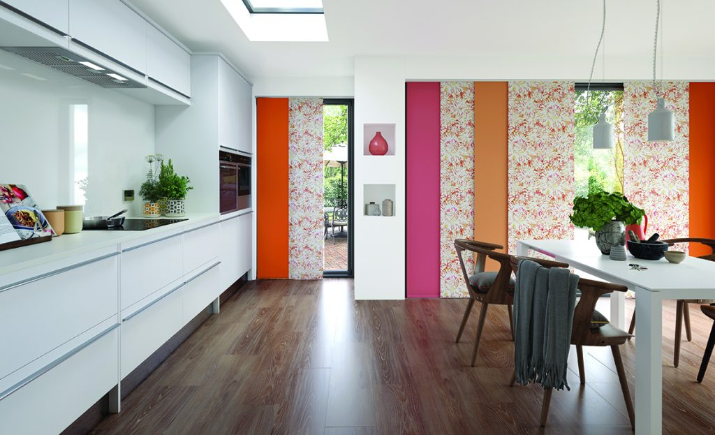 pink, orange and cream patrterned panels in floor to ceiling windows in modern open plan house
