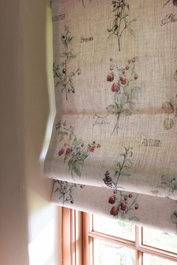 Close up of roman blind with cream background and delicate botanical print
