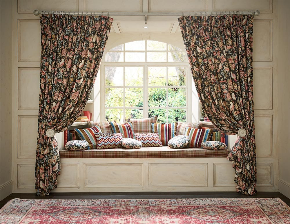 Auburn curtains with tie-backs in a bay window with window seat and cushions.