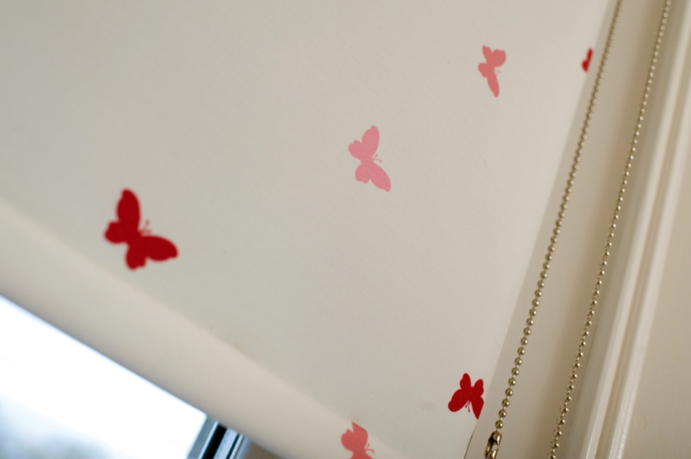 Roller blinds with pink and red butterflies on cream background