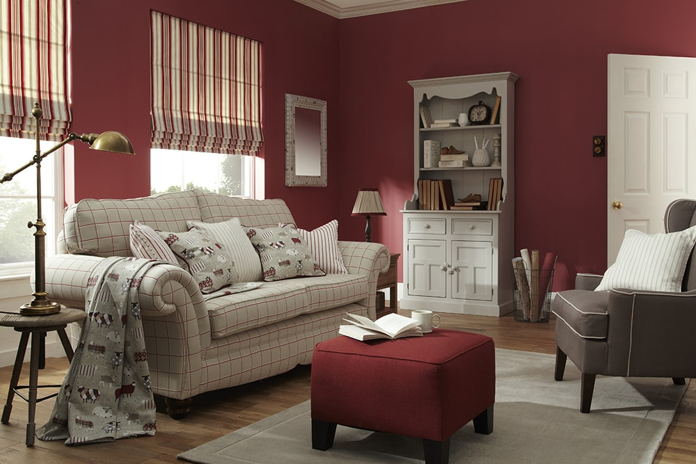 sheep patterned cushions on sofa to complement the red striped roman blinds