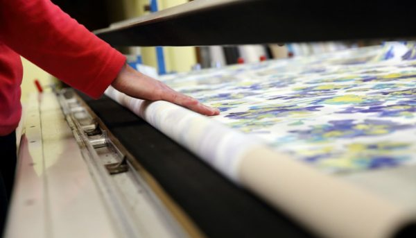 Roller blind fabric being rolled out in our factory ready for cutting