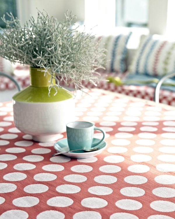 Red and white table cloth with summery striped cushions on seat