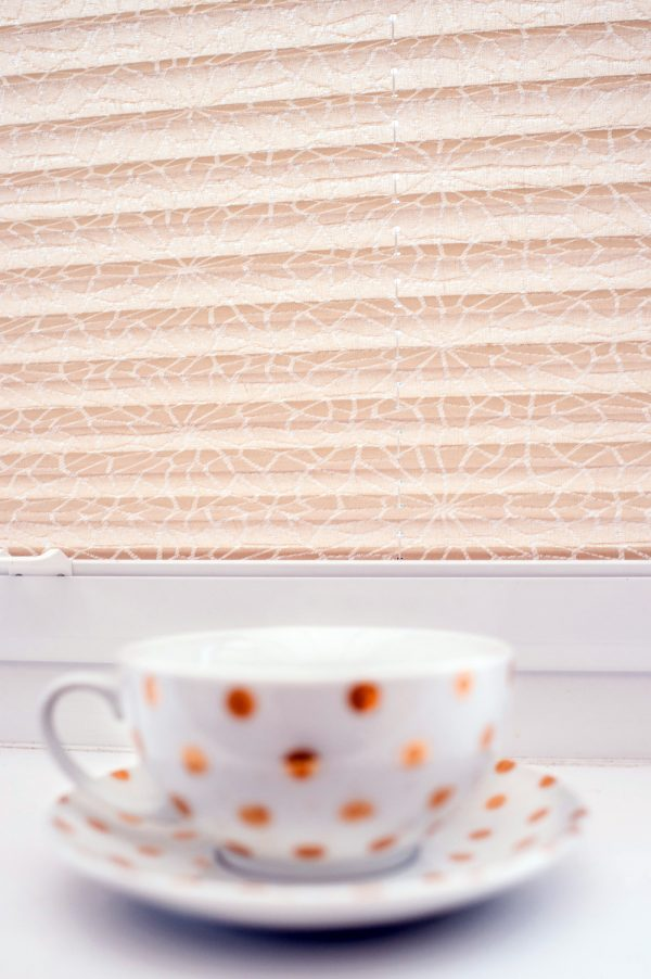 Cup and saucer on windowsill under cream pleated blind