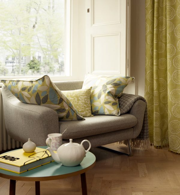 Sofa with cushions made in fabric to co-ordinate with cream curtains
