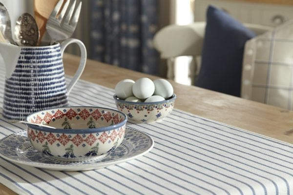 teacup on blue striped table runner and blue curtains in window