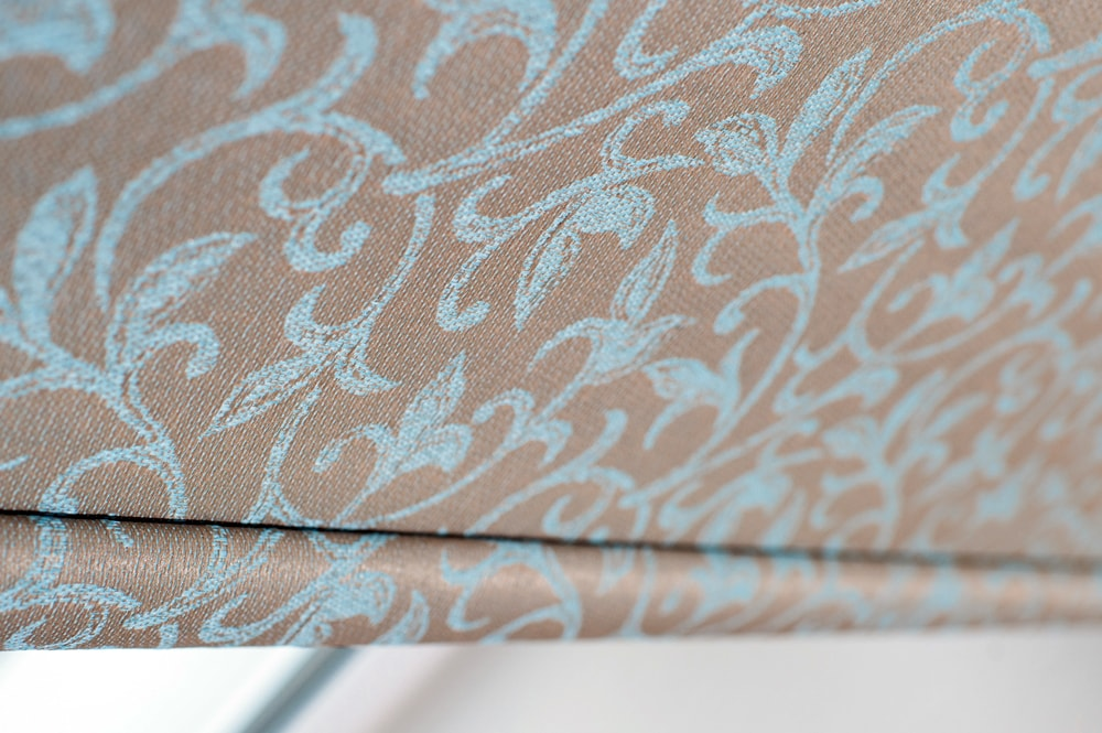 Close up roller blind with velvety tan and light blue design