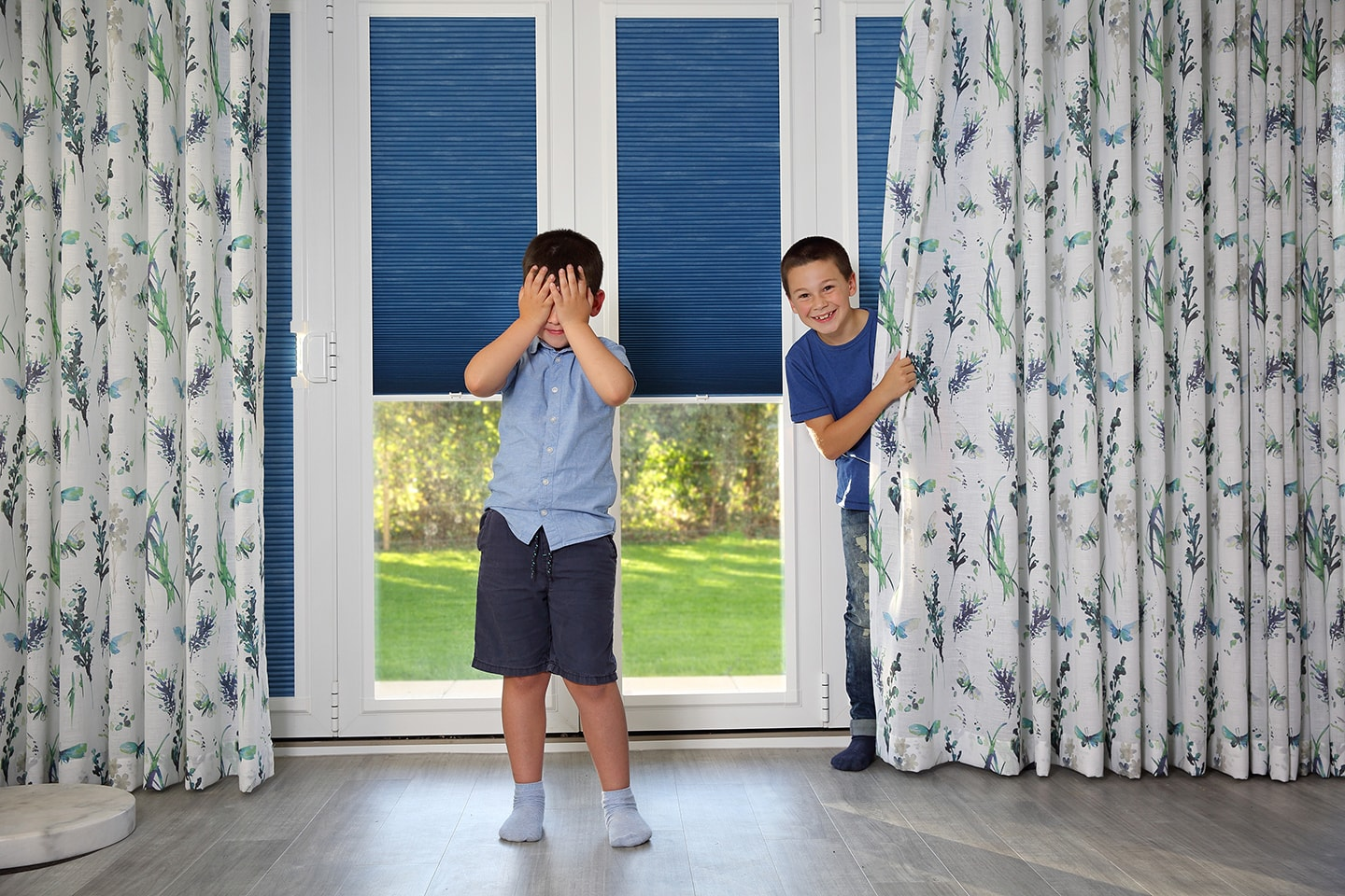 Two boys playing hide and seek with beautiful curtains and perfect fit blinds